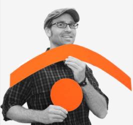 Bild von Torsten Sowada. Er trägt ein Karohemd und Hut. Die Symbole Klammer und Punkt hält er vor dem Oberkörper.