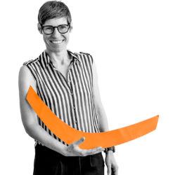 Tanja in schwarz-weiß, hält eine orangene Klammer ) auf dem Arm