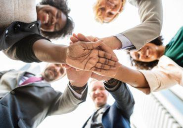 Eine Gruppe von Menschen, die ihre Hände im Mittelpunkt zusammenpacken.