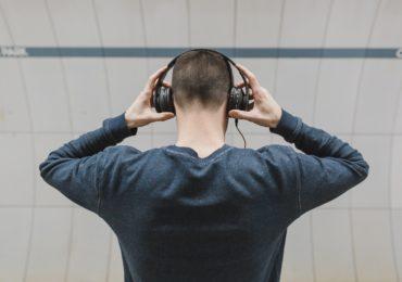 Ein Mann, der von hinten fotografiert wurde und mit Kopfhörern Musik hört.