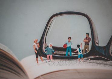 Ein aufgeklapptes Buch, darauf eine Brille. Davor und dahinter kleine Figuren, die sich anschauen und gemeinsam mit einander etwas machen