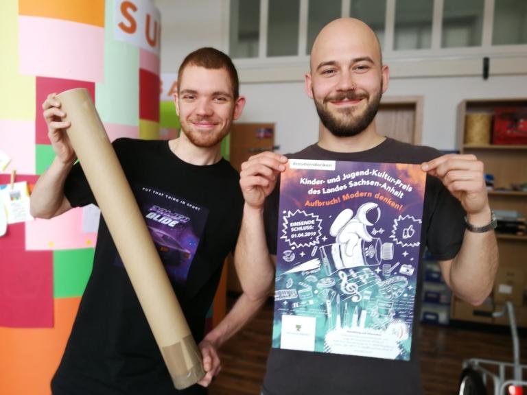 KJKP 2019 – Erste Einsetzung: Perry (rechts) post mit dem KJKP-Plakat, Bennet links daneben mit Versand-Rolle.