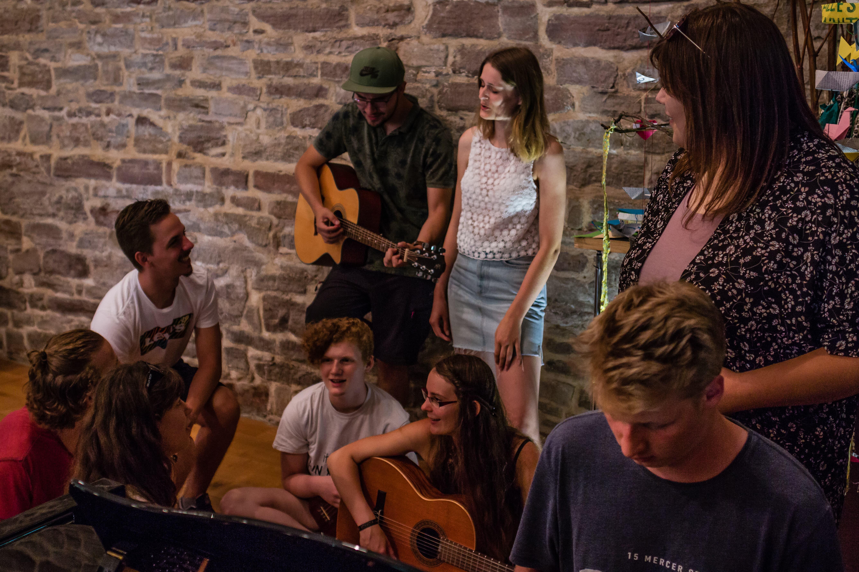Menschen sitzen zusammen und musizieren zusammen.