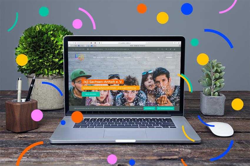 Laptop mit einem Screenshot der neuen .lkj)-Website. Laptop steht auf Schreibtisch. Daneben Pflanzen, Stifte in Halter und Mouse.