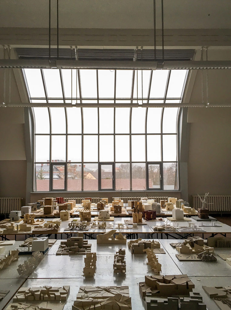 Das Bild zeigt Modelle vor einem großen Fenster.