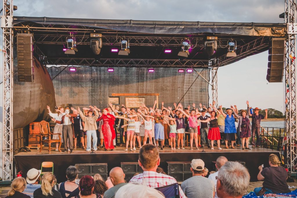 Das Foto zeigt alle Mitwirkenden des Theaterstücks auf der Bühne. Die Gruppe schwingt die Arme über den Köpfen.