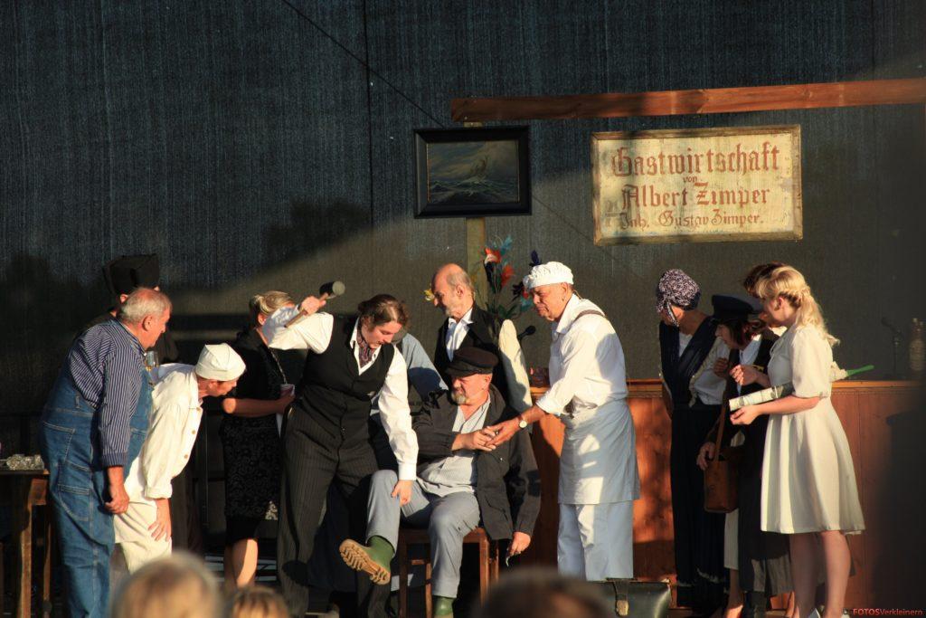 Auf der Bühne befinden sich Darsteller*innen, die eine Krankenszene nachstellen.