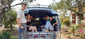 Gruppe von jungen Menschen, die gemeinsam auf der Ladefläche eines Autos sitzen