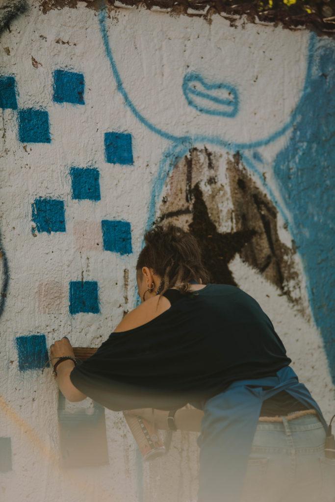 Eine Person besprüht eine Mauer mit blauen Quadraten. Dies ist im Rahmen eines Workshops beim KIEZ Kunst.Aktions.Tag 2020 entstanden.