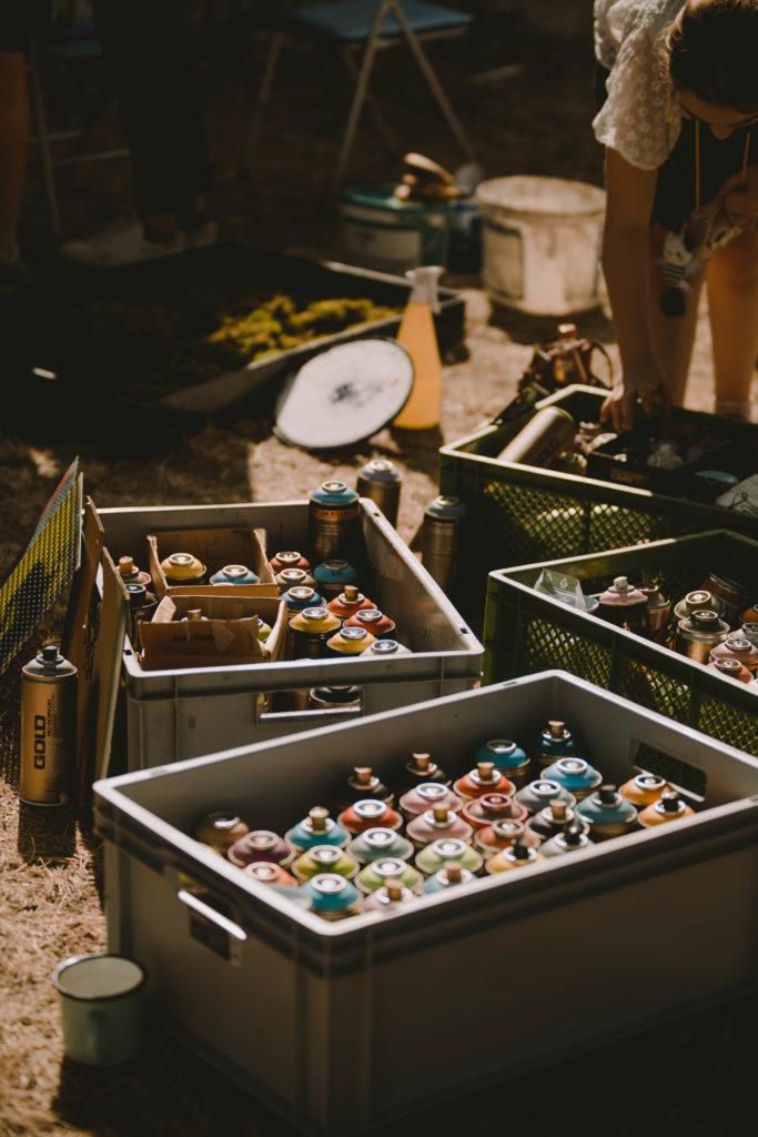 Eine Person wählt eine Spraydose aus vier verschiedenen Kisten voll mit Spraydosen verschiedener Farben.