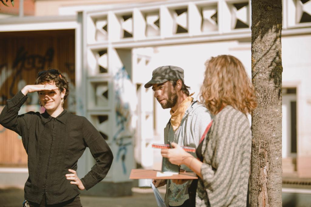 3 Personen stehen vor dem Salbker Lesezeichen, unterhalten sich und schauen sich das Programm an.