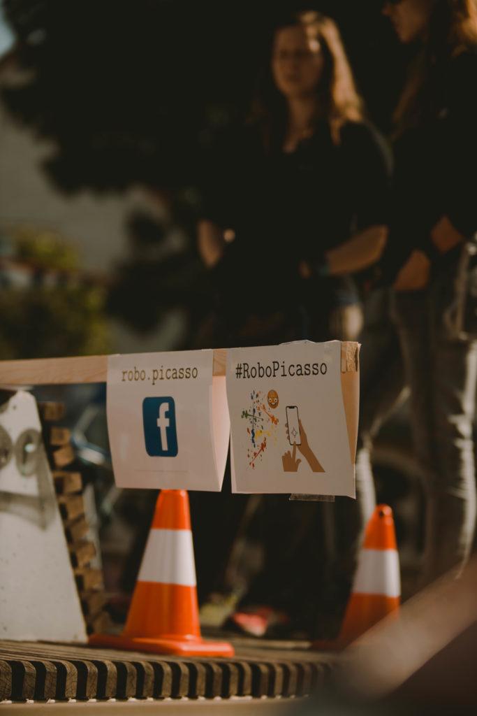 """Im Vordergrund sind zwei Schilder angebracht für einen Facebook-Account von """"robo.picasso"""" und für den Hashtag RoboPicasso."""