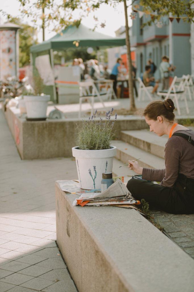 Kiezrebell:in Hanna bemalt einen Blumentop mit Lavendel. Dies ist ein Beitrag zur Straßengalerie in Salbke.