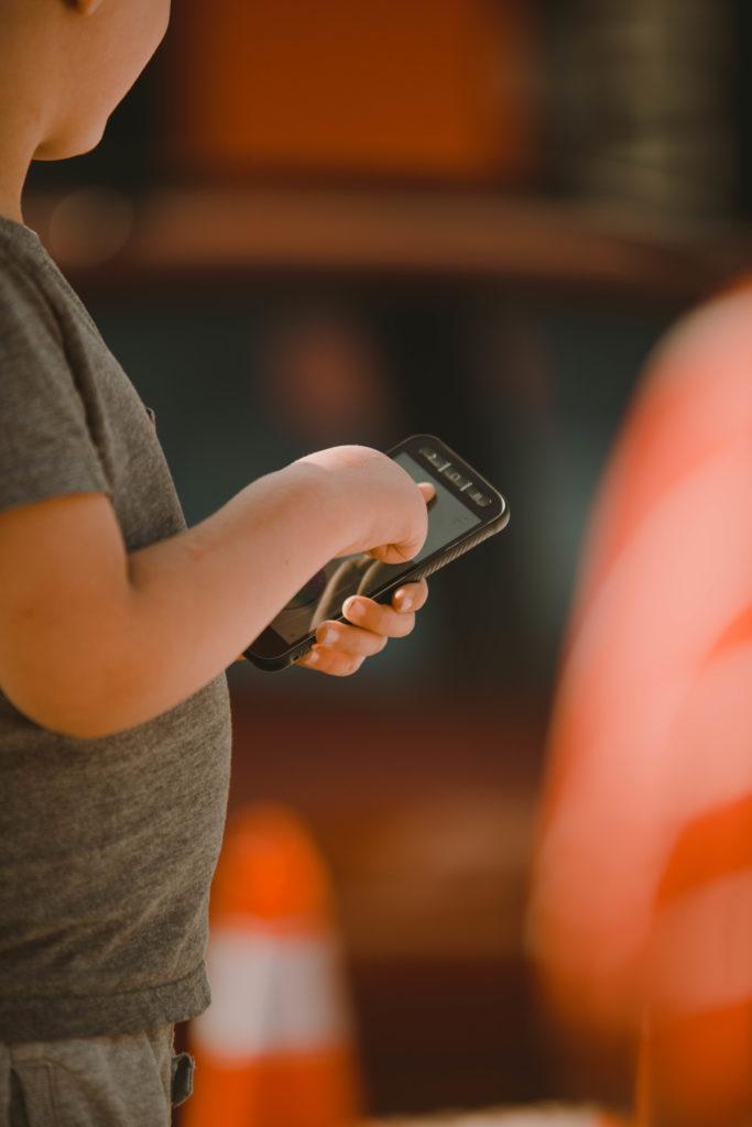 Ein Kind hält ein Smartphone.