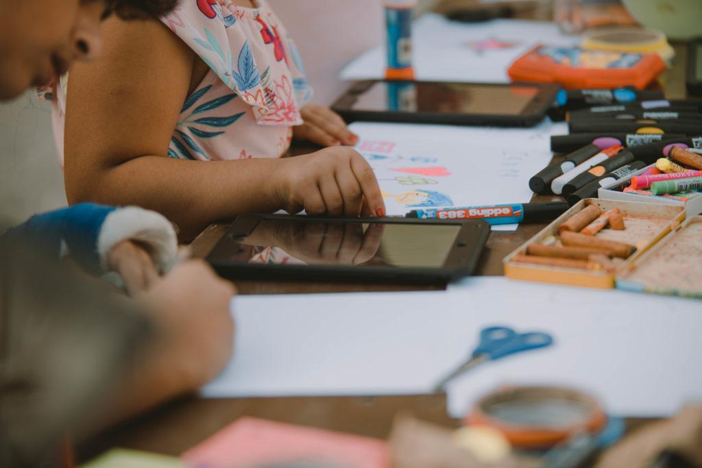 Man sieht die Hände von Kindern beim Malen. Vor ihnen liegen zahlreiche Stifte, Wachsmaler und Papier. Außerdem liegen zwei Tablets auf dem Tisch.