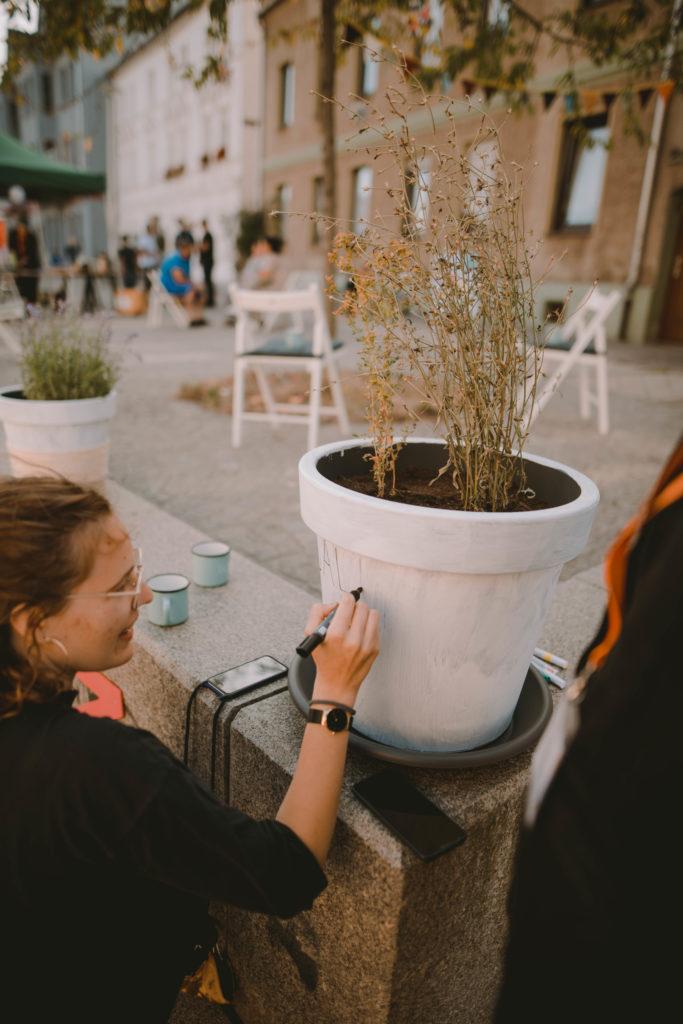 Die Werkstattleitung Franziska Gutkäse bemalt einen Blumentopf im Rahmen der Straßengalerie.