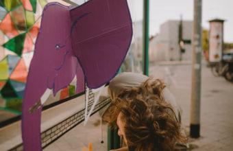 Eine junge Frau beklebt die Scheibe einer Straßenbahnhaltestelle mit verschieden farbigem Klebeband. Auf der Scheibe entsteht ein 3D-Elefantenkopf. Das Bild entstand im Rahmen der Straßengalerie in Magdeburg Südost.