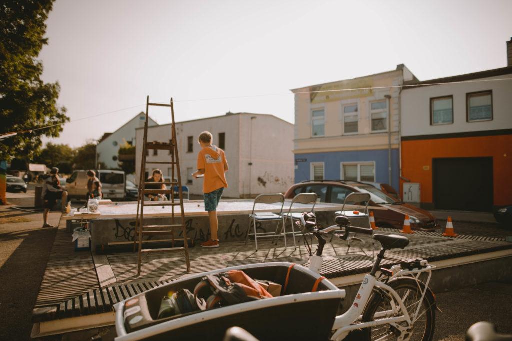 Eine Person macht ein Foto von dem Kunstwerk des RoboPicasso. Im Vordergrund ist ein Lastenfahrrad zu sehen.