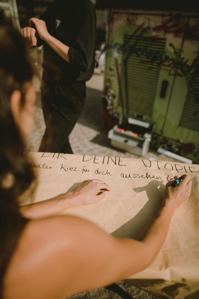"""Eine Person beschreibt ein Plakat auf dem steht: """"Bau dir deine Utopie - Wie soll ein idealer Kiez für dich aussehen?"""""""