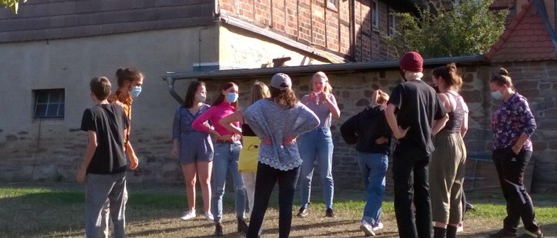 Freiwillige des weltwärts Rückkehrenden-Seminars stehen vor einem Gebäude im Kreis. Sie tragen einen Mund-Nasen-Schutz und unterhalten sich.