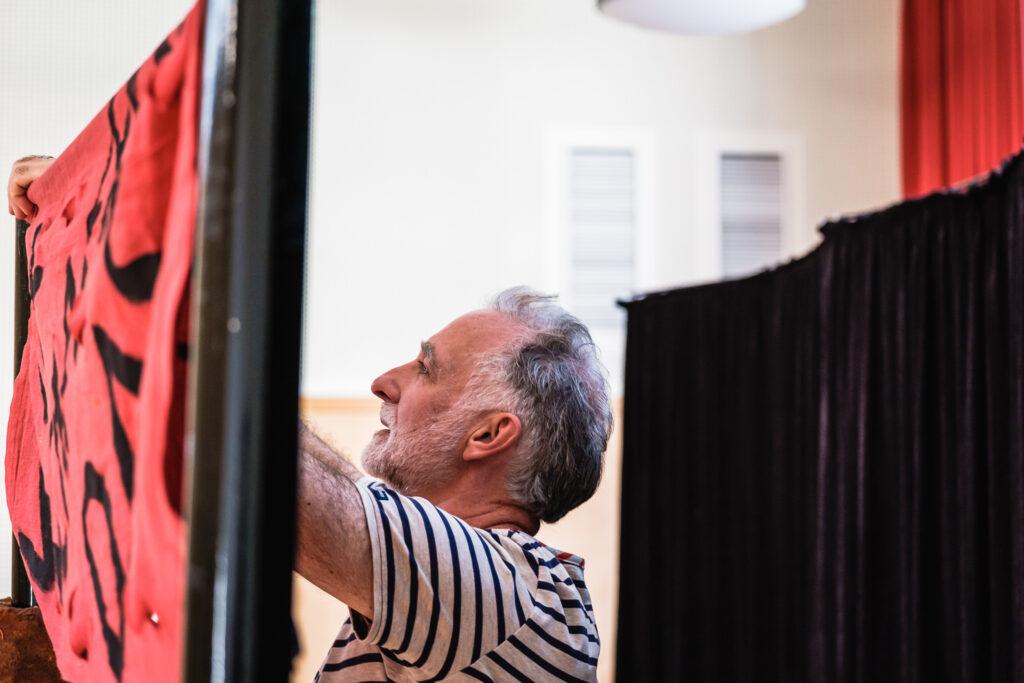 Ein älterer Mann steht an einer Leinwand und spannt einen Stoff auf. Hinter ihm sieht man einen dunklen Theatervorhang.